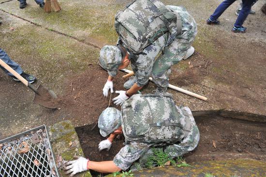 驻港部队官兵用手疏通排水渠堵塞。(图片来源:中央政府驻港联络办)